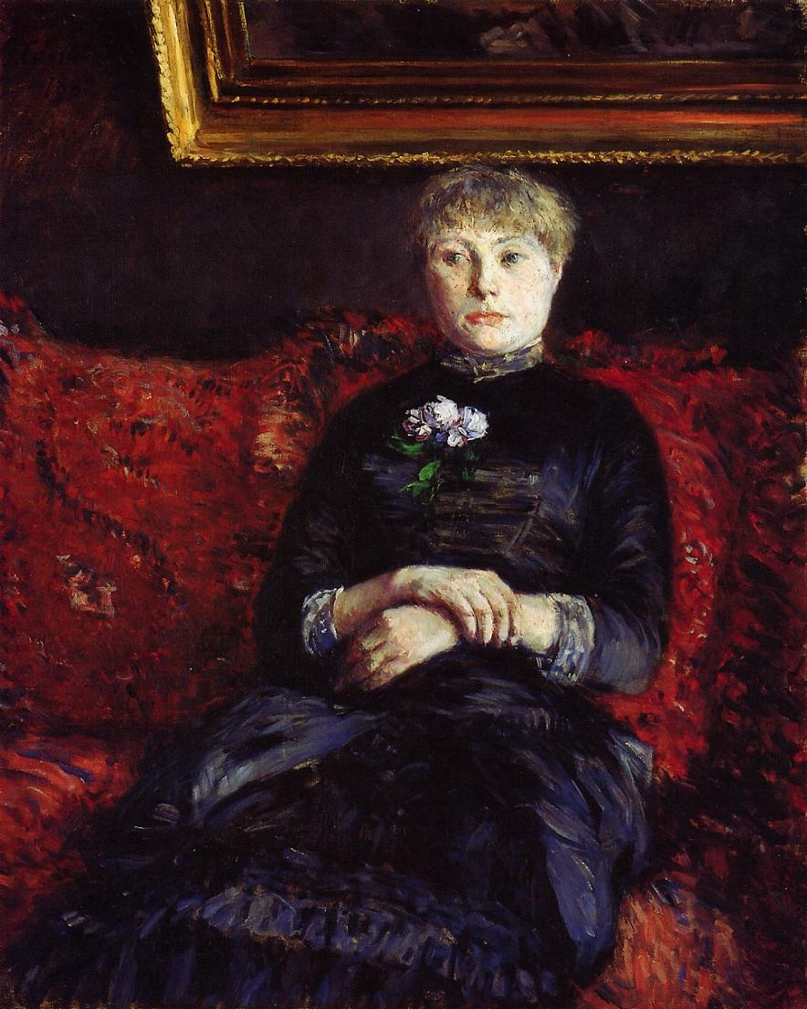 woman-sitting-on-a-red-flowered-sofa